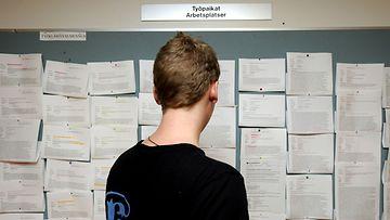 Nuori mies tutkii ilmoitustaulua työnhakukeskuksessa.