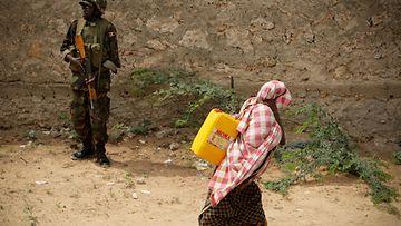 Avustusjärjestöt yrittävät auttaa Somalian kuivuudesta kärsivää kansaa, mutta tilanne on vaikea. Somalinainen kantaa vettä YK-sotilaan edessä Mogadishussa Somaliassa 15.7.2011 Kuva: EPA
