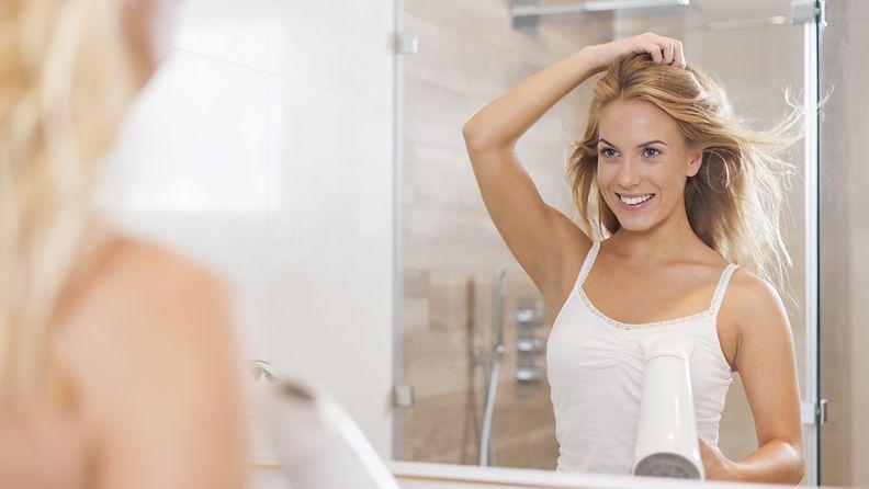 Nainen-kuivaa-hiuksiaan-salin-jälkeen