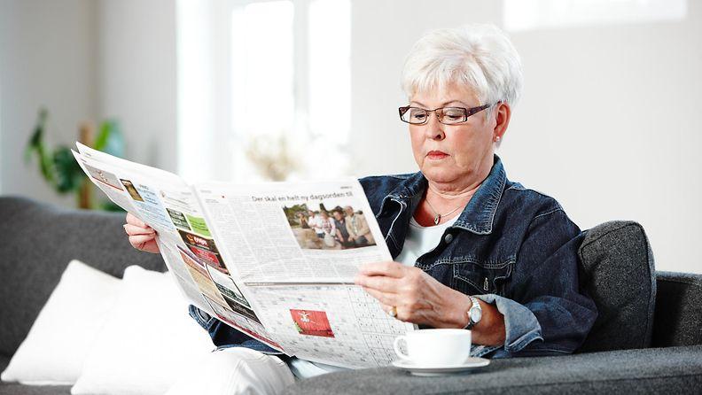 vanhempi nainen lukee lehteä