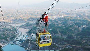 Joulupukiksi pukeutunut henkilökunnan jäsen jakaa hlahjoja turisteille hurjassa paikassa Pingjangissa, Kiinassa.