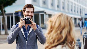Mies ottaa kuvaa naisesta