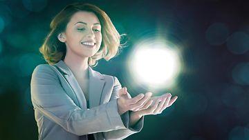 Nainen pitelee valoa kädessään
