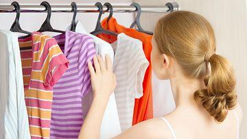 Nainen käy läpi henkaroituja vaatteita