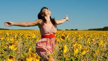 Nainen juoksee auringonkukissa