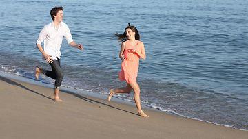 Pariskunta juoksee rannalla