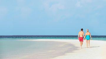 Pari kävelee meren rannalla