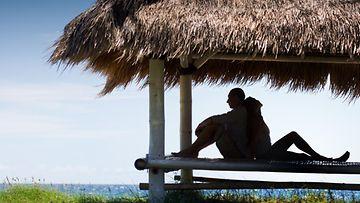 Pari istuu varjossa rannalla