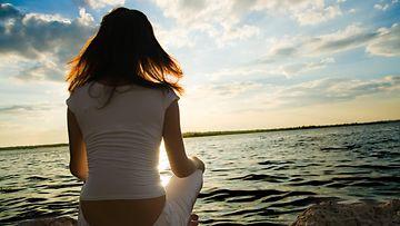 Meditoiva nainen meren rannalla