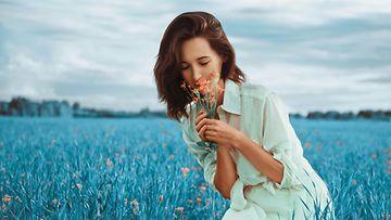 Nainen poimii kukkia
