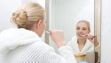 Nainen pesee hampaat