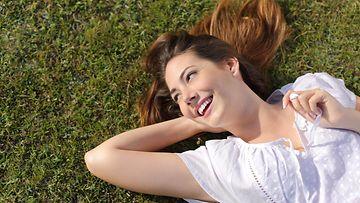 Nainen makaa nurmella
