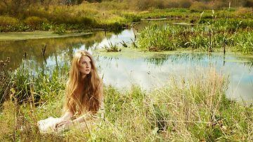 Nainen metsässä lammen rannalla