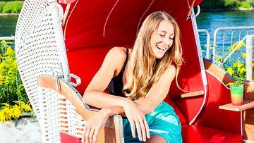 Nainen nauraa tuolissa