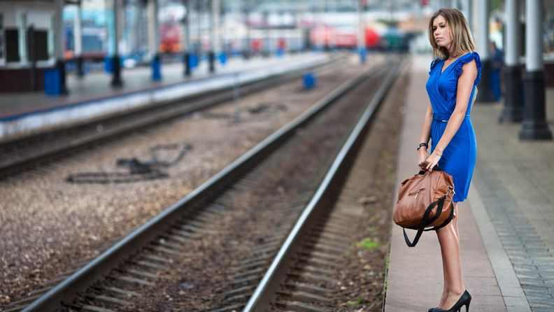 Nainen odottaa junaa