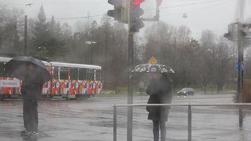 Ihmisiä sateessa