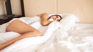 Nainen makaa sängyssä
