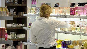 Kosmetiikkaosaston myyjä järjestelee myyntihyllyjä.