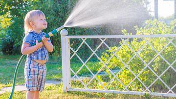 Lapsi kastelee pihaa