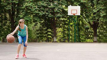 Tyttö pelaa koripalloa
