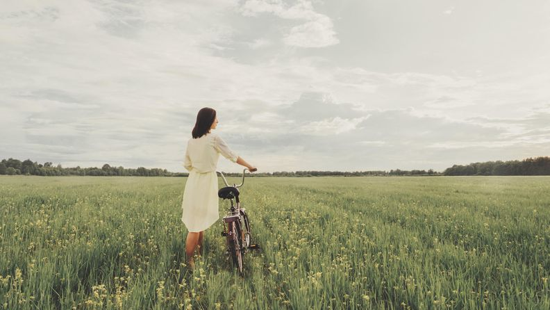 Nainen pellolla pyörän kanssa