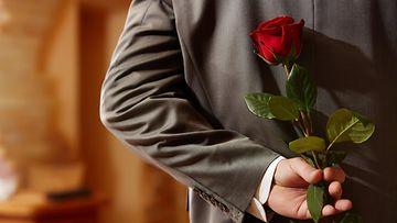 Mies ruusu selän takana