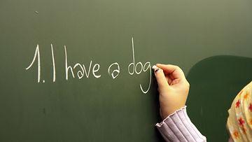 Lapsi kirjoittaa taululle koulussa