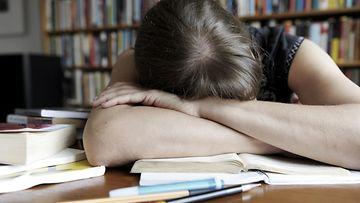 Lapsi väsyneenä läksyjen kanssa