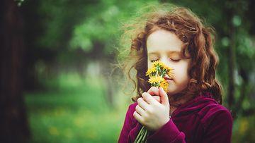 Tyttö haistelee kukkia