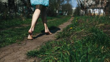 Nainen kävelee paljain jalon