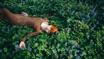 Nainen nukkuu metsässä