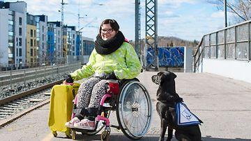 Avustajakoiran käyttäjä matkalla koiran kanssa.