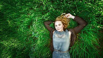 Nainen makaa nurmella metsässä