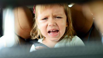 Lapsi vihaisena auton takapenkillä.