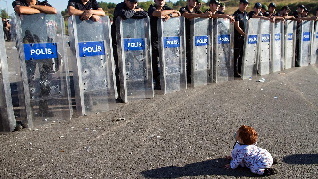 Turkissa pieni syyrialaisvauva konttaili mellakkapoliisirivistön edessä Istanbulin ja Edirnen välisellä maantiellä, kun pakolaiset odottivat lupaa Turkin ja Kreikan välisen rajan ylitykseen 19. syyskuuta 2015. Copyright: EPA. Kuva: TOLGA BOZOGLU.