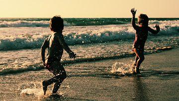 Lapset leikkivät rannalla. Tällainen kuva kelpaa myös pedofiilille. Kuvituskuva.