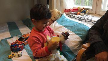 Kolmevuotias Ali leikkii perheensä huoneessa