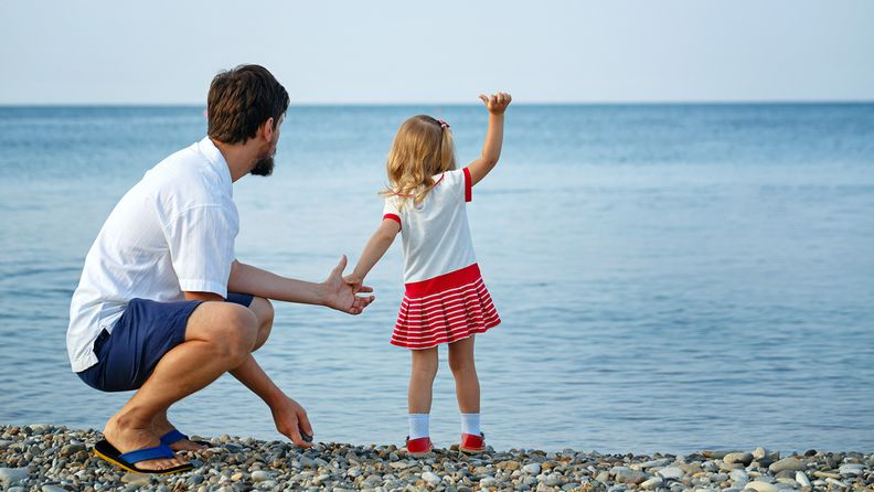 Isä ja tytär meren rannalla