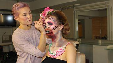 Emma Räsänen loihtii mallilleen Sugar Skull -meikkiä.