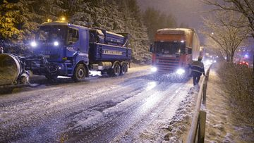 Hiekoitusauto työssään ja poliisi ohjaamassa liikennettä kun rekkoja jumissa huonon kelin takia Kehä I:sen kohdalla Espoon Otaniemessä perjantaina 21. marraskuuta 2014.