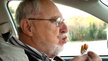Mies ruokailee autossa.