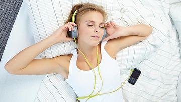 Nainen makaa, kuulokkeet