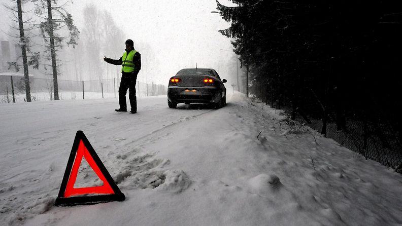 Huomioliivejä käyttävä mies kävi laittamassa varoituskolmio tielle, koska hänen autonsa jäi tienposkeen, Helsingissä 22. joulukuuta 2009. (Lavastus)
