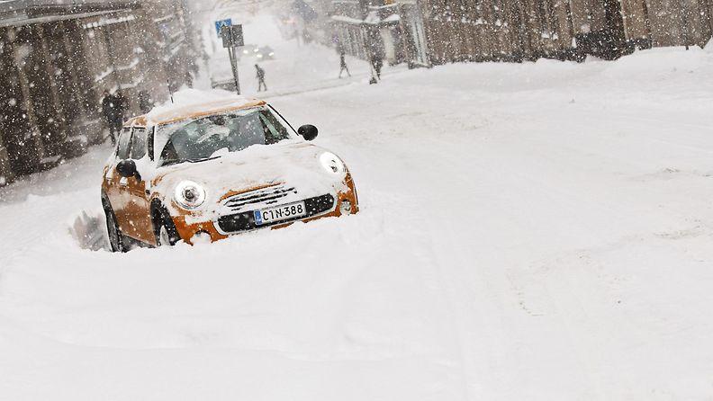 Auto jumissa lumikinoksissa Fabianinkadulla Helsingissä tiistaina 12. tammikuuta 2016.