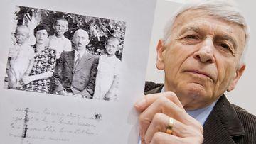 Auschwitzista selvinnyt Max Eisen näyttää perheensä valokuvaa, joka on otettu 1940-luvulla.