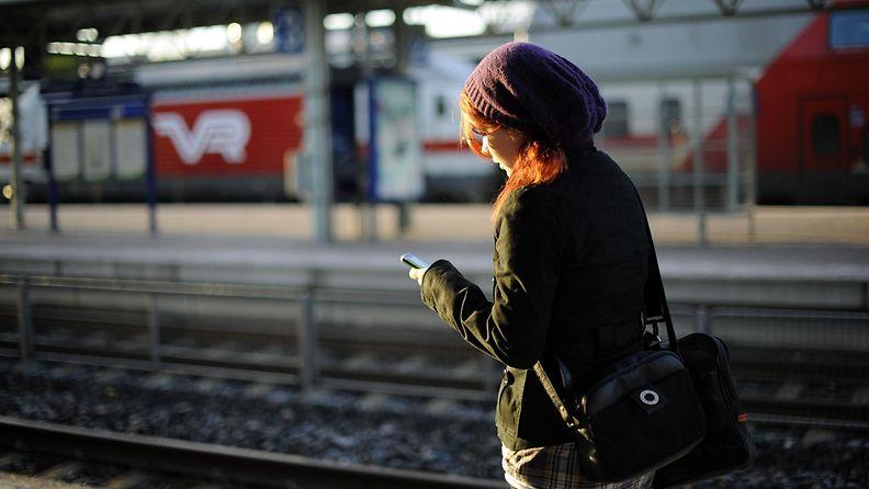 nainen käyttää puhelinta juna-asemalla