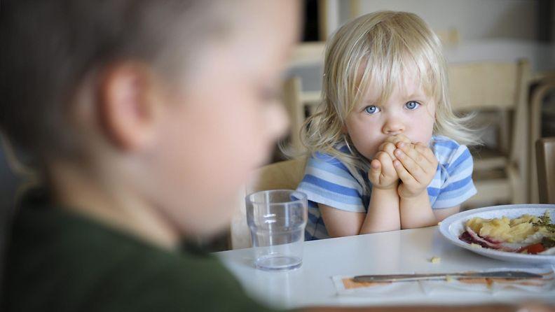 2-vuotias Wilhelmiina Koskinen syö pinaattilettuja Tuomarilan päiväkodissa Espoossa 6. elokuuta 2013. Etualalla 3-vuotias Lukas Louhento. LEHTIKUVA Aleksi Tuomola