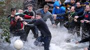 Competitors from the opposing teams, the Up'ards and the Down'ards, reach for the ball during the annual Royal Shrovetide Football Match in Ashbourne, northern England, on February 9, 2016. The mass-participation ball game involves two teams, whose players are defined by which side of a small brook that bisects the town they were born, aiming to score a goal, which are some three miles apart. The game, which has very few rules, is played over two 8 hour periods on Shrove Tuesday and Ash Wednesday. Royal Shrovetide Football is believed to have been played annually in Ashbourne since 1667.
