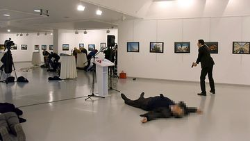 "This picture taken on December 19, 2016 shows Andrey Karlov (2ndR), the Russian ambassador to Ankara, lying on the floor after being shot by a gunman (R) during an attack during a public event in Ankara. A gunman crying ""Aleppo"" and ""revenge"" shot Karlov while he was visiting an art exhibition in Ankara on December 19, witnesses and media reports said."
