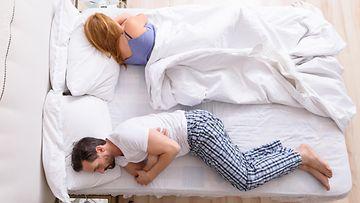 pariskunta sängyssä erillään